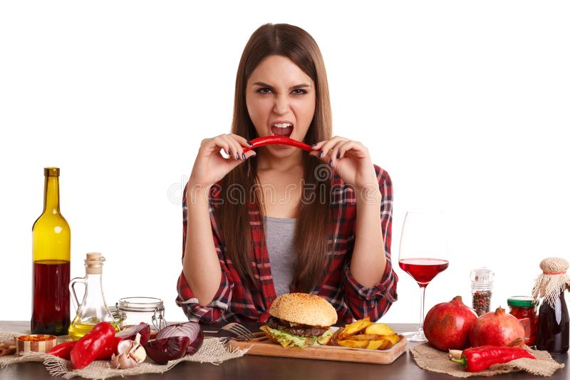 Händchenhalten roter Paprika und Versuche eines Mädchens, zum es mit weit offenem Mund zu beißen Getrennt auf weißem Hintergrund lizenzfreie stockfotos