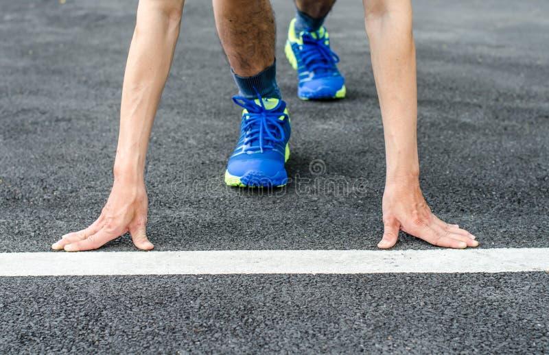 Hände auf Anfangszeile, männlicher Läufer ist im Begriff zu beginnen zu laufen lizenzfreie stockfotografie