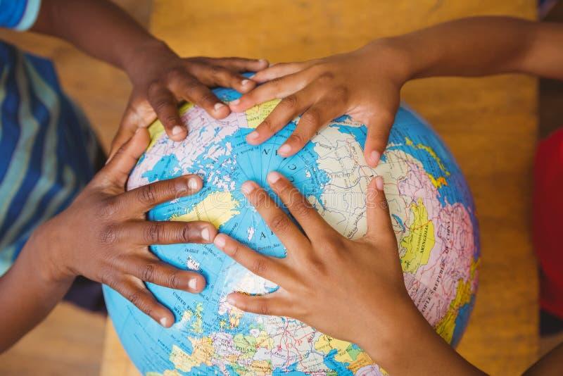 Hände auf Kugel im Klassenzimmer lizenzfreie stockbilder