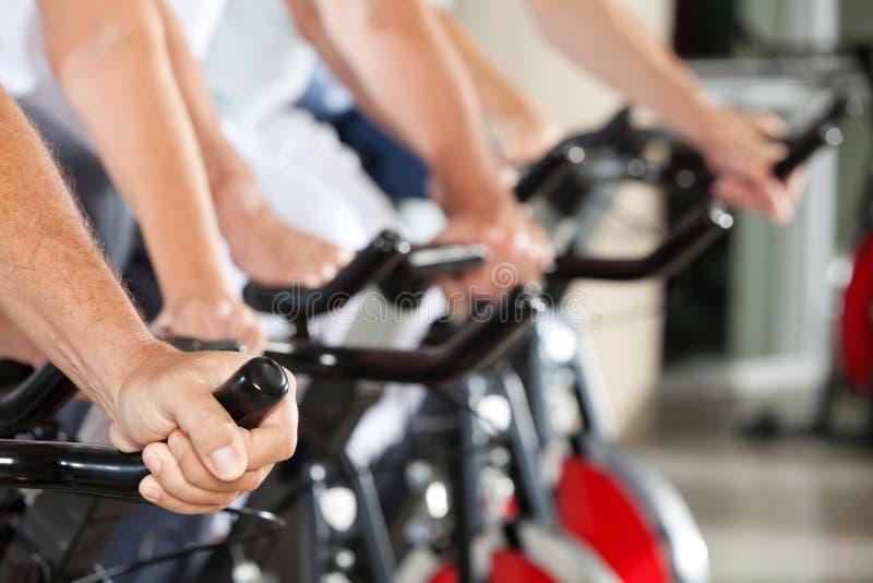 Hände auf spinnenden Fahrrädern in der Eignung stockfotografie