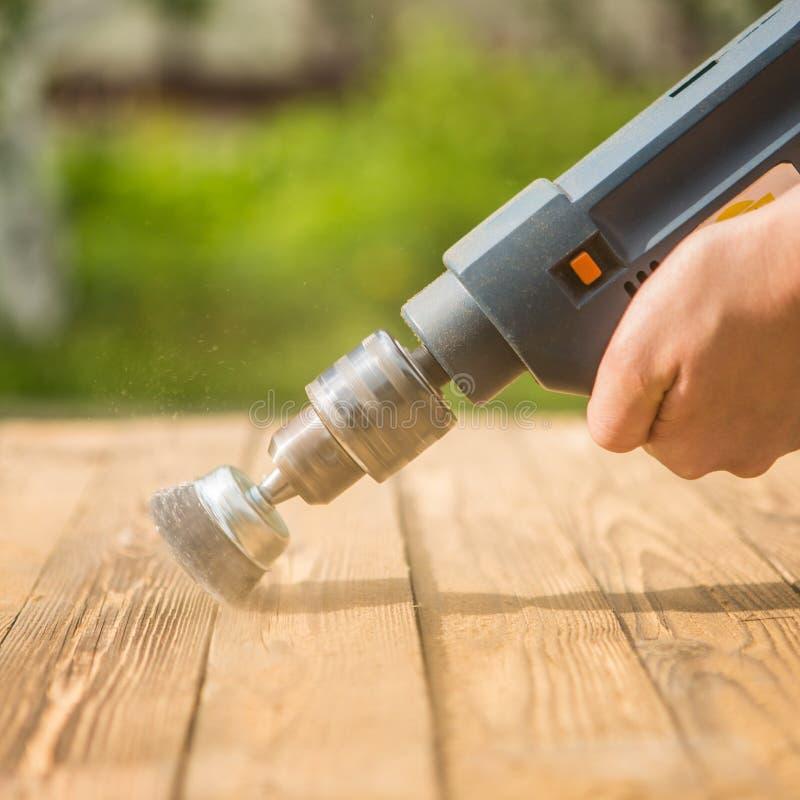 Hände bemannen mit der elektrischen drehenden Bürstenmetallscheibe, die ein Stück Holz versandet stockfoto