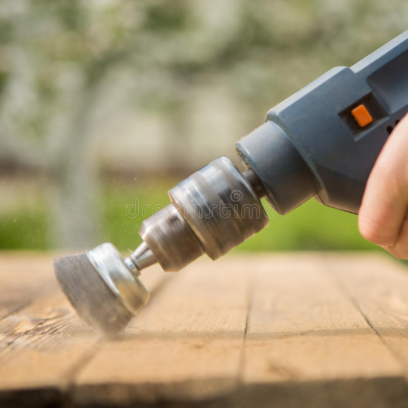 Hände bemannen mit der elektrischen drehenden Bürstenmetallscheibe, die ein Stück Holz versandet lizenzfreies stockfoto