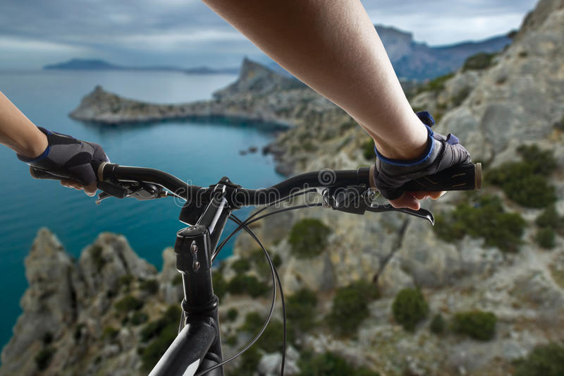 Hände in den Handschuhen, die Lenkstange eines Fahrrades anhalten Mountainbikeradfahrer, der einzelne Bahn reitet Aktives Athlete lizenzfreies stockfoto