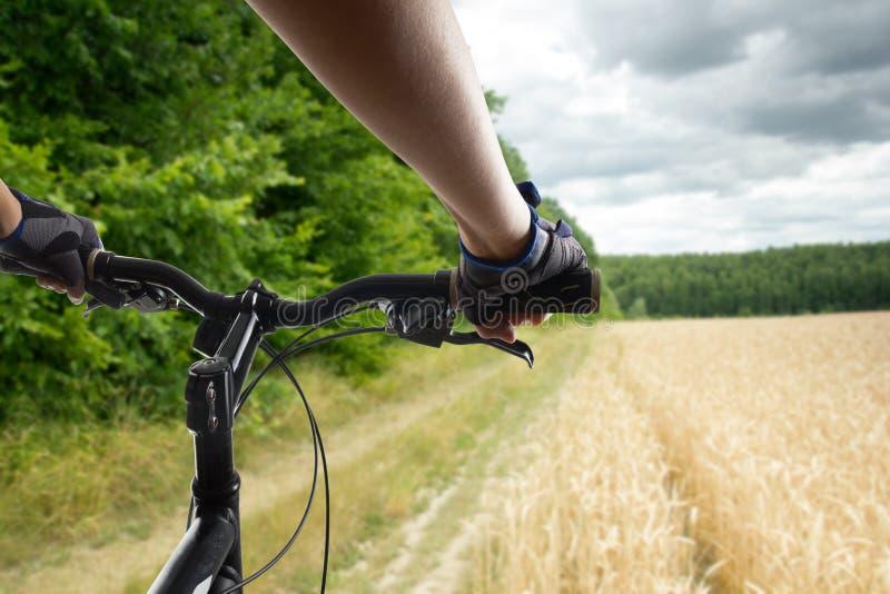 Hände in den Handschuhen, die Lenkstange eines Fahrrades anhalten Mountainbikeradfahrer, der einzelne Bahn reitet Gesunder Lebens stockbild