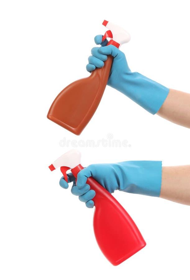 Hände in den Handschuhen hält Sprühflaschen. stockfotografie