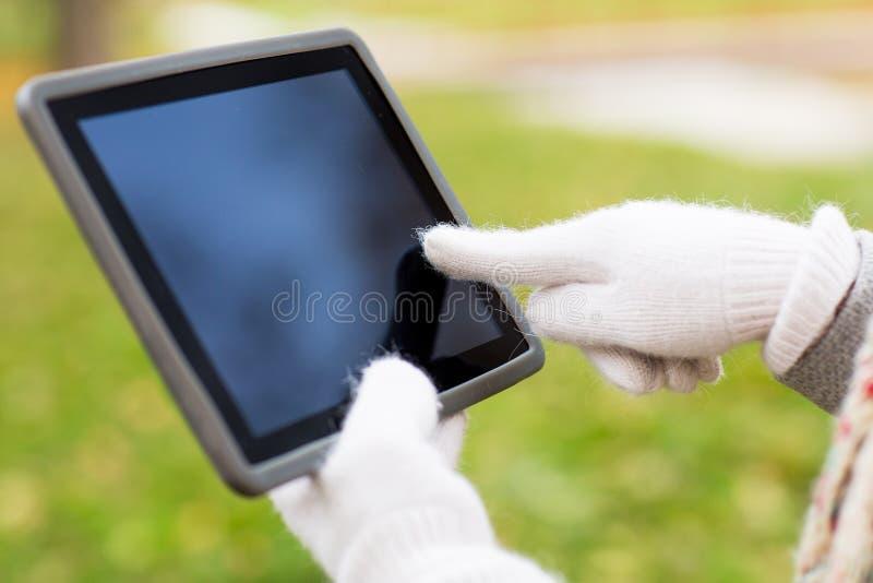 Hände in den Herbsthandschuhen, die draußen Tabletten-PC halten lizenzfreie stockfotografie