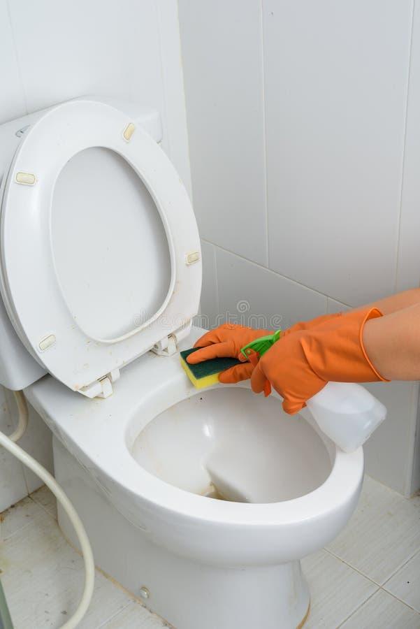 Hände in den orange Handschuhen, die WC, Toilette, Toilette säubern lizenzfreies stockfoto