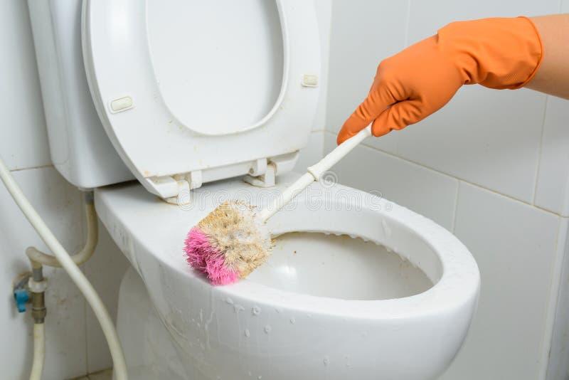 Hände in den orange Handschuhen, die WC, Toilette, Toilette unter Verwendung der Bürste säubern stockfotos