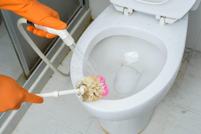 Hände in den orange Handschuhen, die WC, Toilette, Toilette unter Verwendung der Bürste säubern lizenzfreie stockfotografie