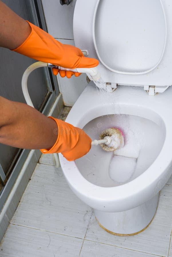 Hände in den orange Handschuhen, die WC, Toilette, Toilette unter Verwendung der Bürste säubern lizenzfreies stockfoto