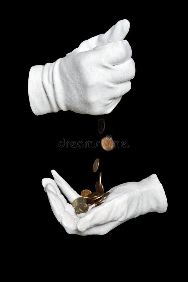 Hände in den weißen Handschuhen gießen feine Münzen stockbilder