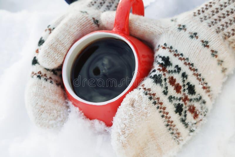 Hände in den woolen Handschuhen halten einen roten Becher mit dem heißem Tee oder Kaffee und stehen auf dem Schnee Konzept der Er stockbilder