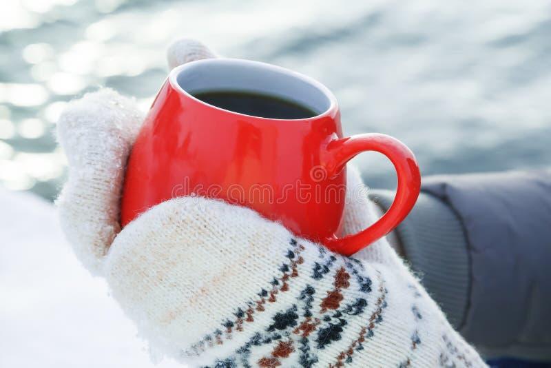 Hände in den woolen Handschuhen halten einen roten Becher mit dem heißem Tee oder Kaffee und stehen auf dem Schnee Konzept der Er lizenzfreie stockbilder