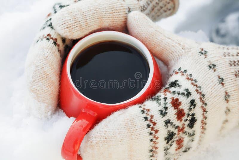 Hände in den woolen Handschuhen halten einen roten Becher mit dem heißem Tee oder Kaffee und stehen auf dem Schnee Konzept der Er lizenzfreies stockbild