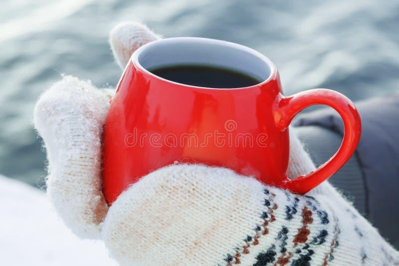 Hände in den woolen Handschuhen halten einen roten Becher mit dem heißem Tee oder Kaffee und stehen auf dem Schnee Konzept der Er stockfotos