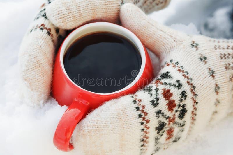 Hände in den woolen Handschuhen halten einen roten Becher mit dem heißem Tee oder Kaffee und stehen auf dem Schnee Konzept der Er stockfotografie