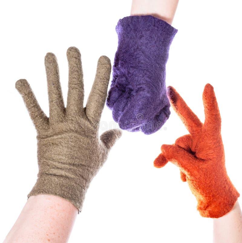 Hände in den woolen Handschuhen stellen Schere, Stein, Papier dar lizenzfreie stockfotografie