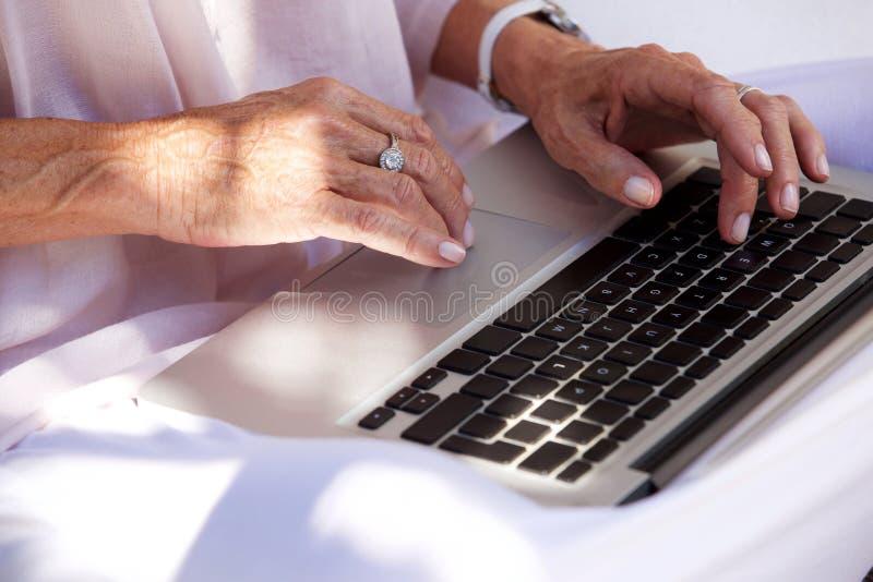 Hände der älteren Frau, die auf Laptop-Computer schreiben stockfoto