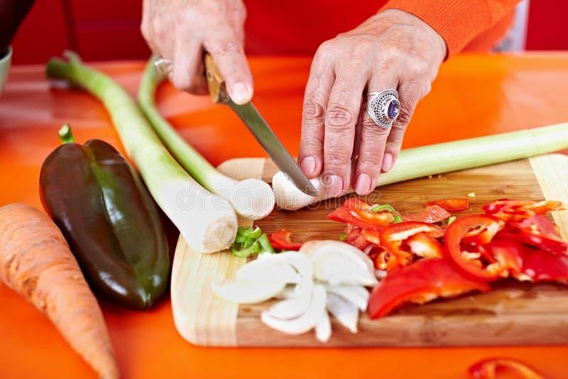 Hände der älteren Frau, die Gemüse schneiden lizenzfreie stockfotografie