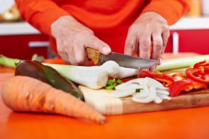 Hände der älteren Frau, die Gemüse schneiden lizenzfreie stockbilder