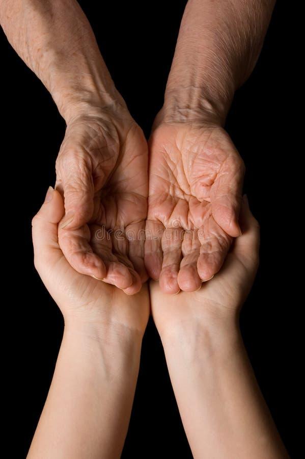 Hände der alten Frau auf Schwarzem lizenzfreie stockfotografie