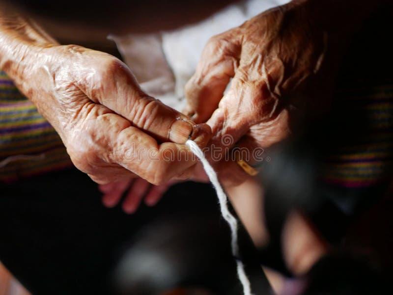 Hände der alten Frau weiße Schnur Sai Sin um ihre Enkelinhände binden - thailändischer traditioneller Segen von einem Ältesten ei lizenzfreie stockfotos