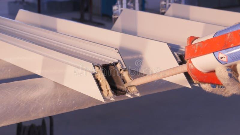 Hände der Arbeitskraft, die ein Silikonrohr für die Reparatur des Fensters Innen verwendet Fensterdetails vom Aluminium Nette Aus stockfotos