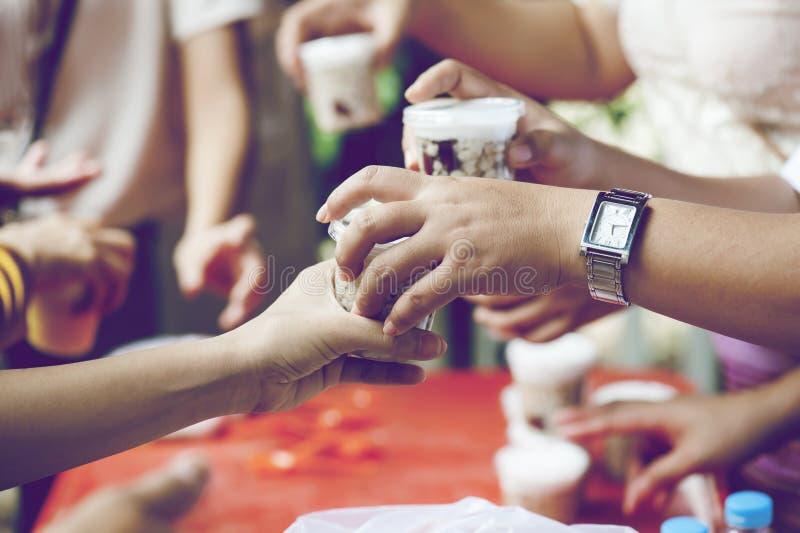 Hände der Armen empfangen Lebensmittel vom Spender-` s Anteil Armutkonzept lizenzfreies stockbild