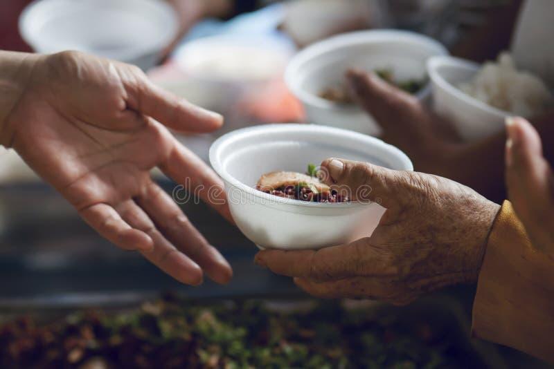 Hände der Armen empfangen Lebensmittel vom Spender-` s Anteil Armutkonzept lizenzfreie stockfotografie