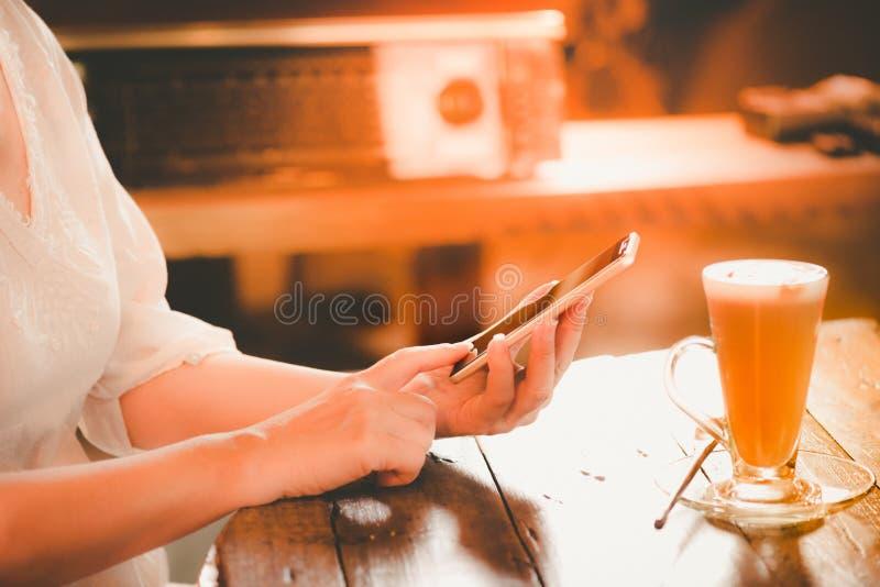 Hände der berufstätigen Frau klicken intelligentes Telefon an der Weinleseartkaffeestube lizenzfreies stockbild