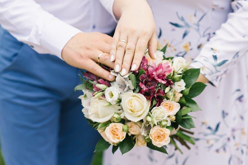 Hände der Braut und des Bräutigams mit Eheringen liegen auf dem Heiratsblumenstrauß von hellen Blumen lizenzfreie stockbilder