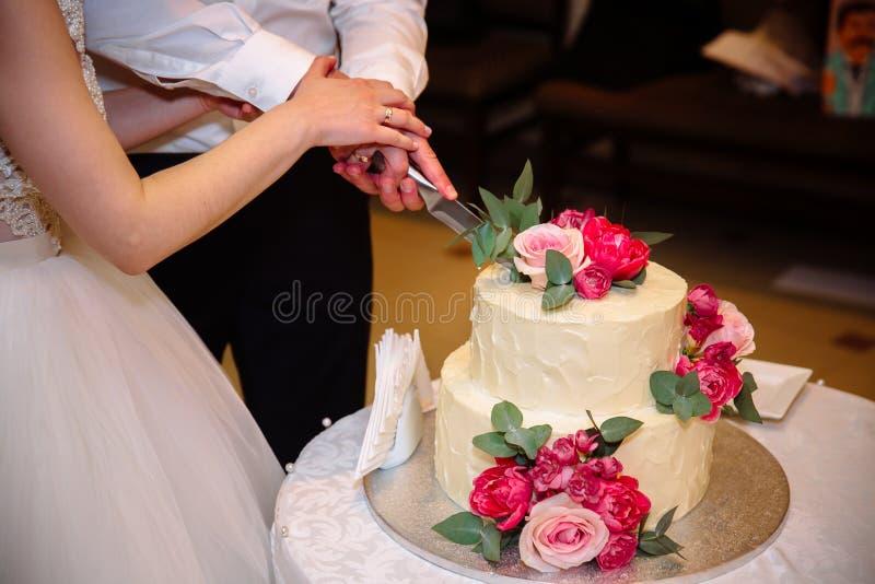 Hände der Braut und des Bräutigams schnitten süße Hochzeitstorte Konzept der Werbungslandschaft des Lebensmittels und der Nachtis lizenzfreies stockfoto