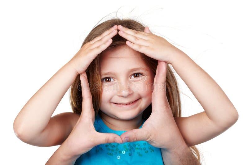 Hände in der Form des Hauses um Mädchengesicht stockfotos