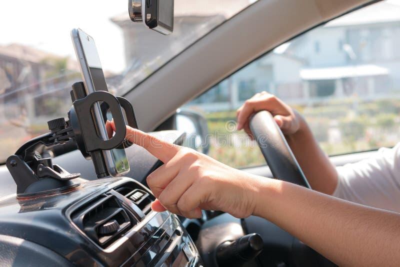 Hände der Frau, die intelligentes Mobiltelefon im Auto für bewegliches te verwendet lizenzfreie stockbilder