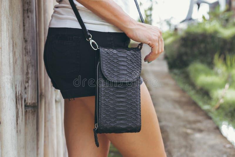 Hände der jungen Frau mit stilvoller Luxus-snakeskin Pythonschlangenhandtasche draußen Bali-Insel stockbilder