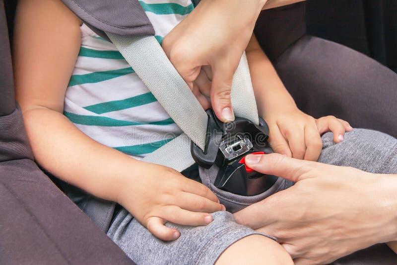 Hände der kaukasischen Frau befestigt Sicherheitsbel lizenzfreie stockfotos