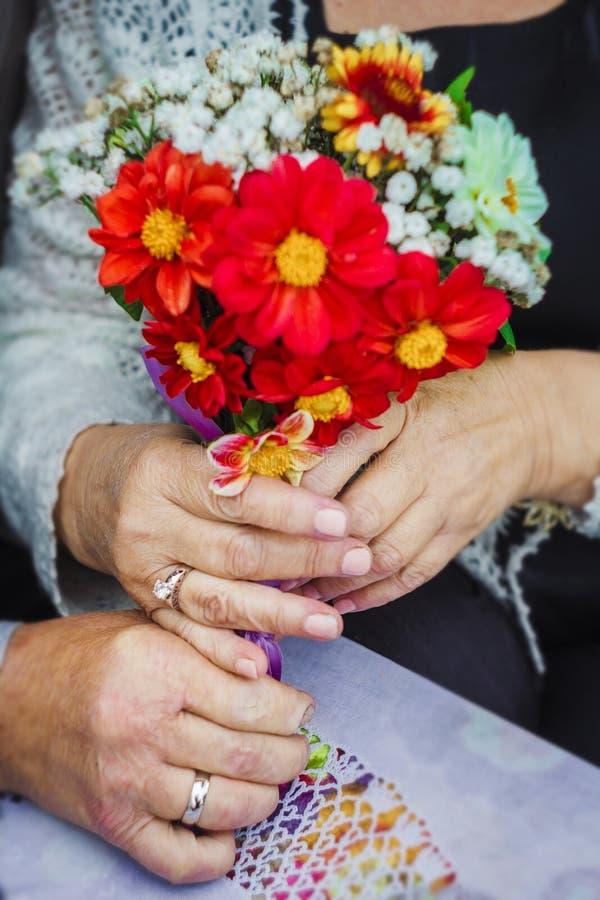 Hände in der Nahaufnahme schossen Ringblumenältere menschen Ehering-Hochzeitstag lizenzfreies stockfoto