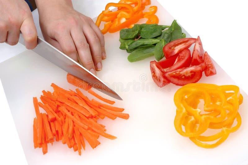 Hände des Chefs, die Gemüse schneiden lizenzfreie stockbilder