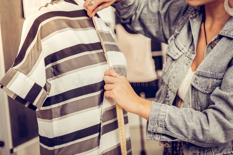 Hände des Designers ein Kleid mit einem Maßband messend lizenzfreie stockfotos