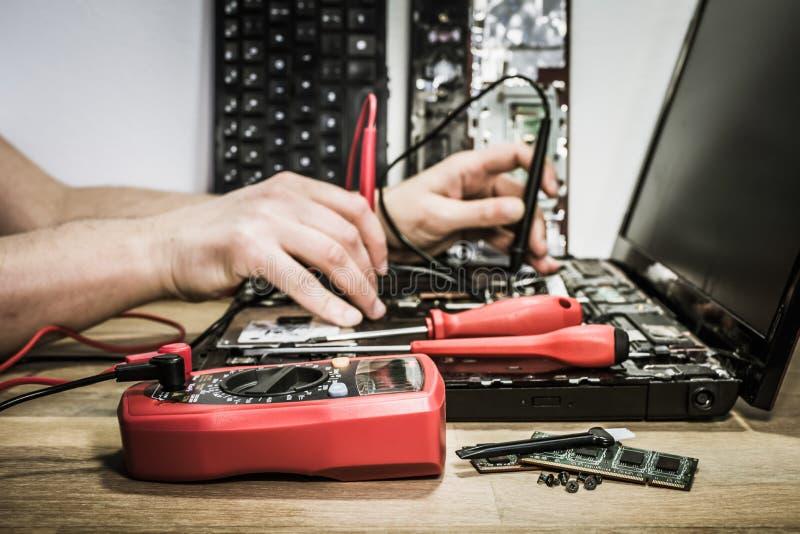 Hände des Elektronik-Ingenieurs gebrochenen Laptop reparierend lizenzfreie stockfotos