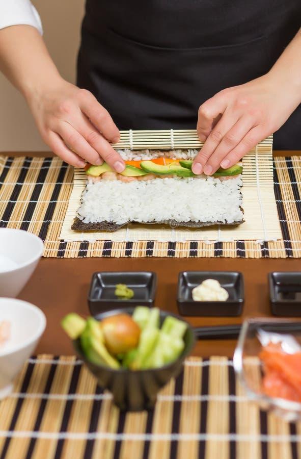 Hände des Frauenchefs rollend herauf ein japanisches Sushi stockbilder