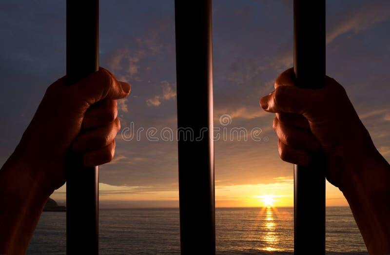 Hände des Gefangenen mit dem Sonnenuntergang im Hintergrund lizenzfreies stockbild