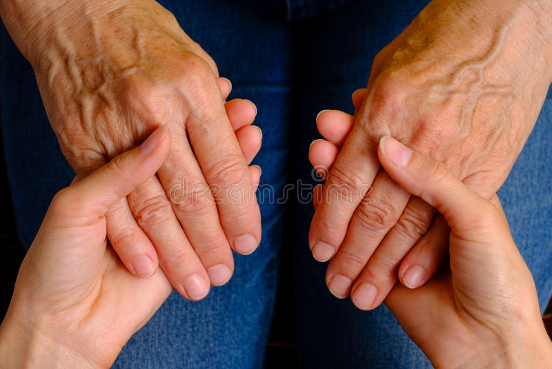 Hände des Händchenhaltens der jungen Frau einer älteren Frau stockbild