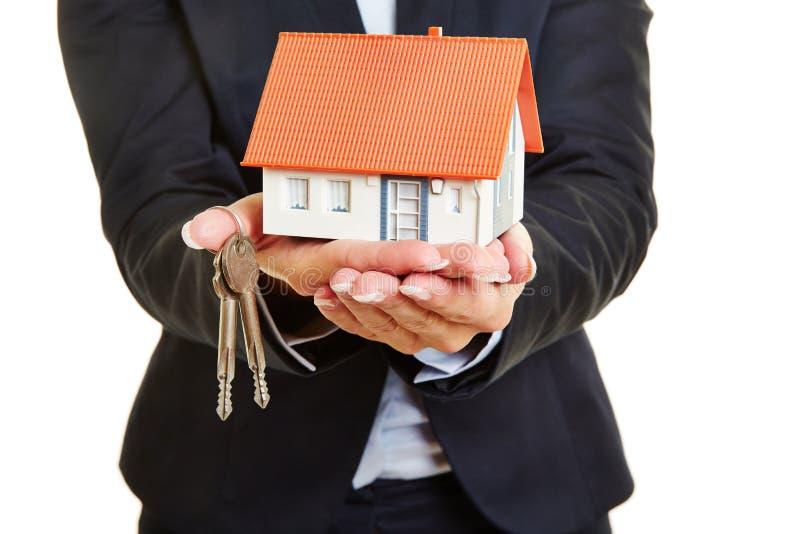 Hände des Immobilienmaklers mit Haus und Schlüsseln stockfotos
