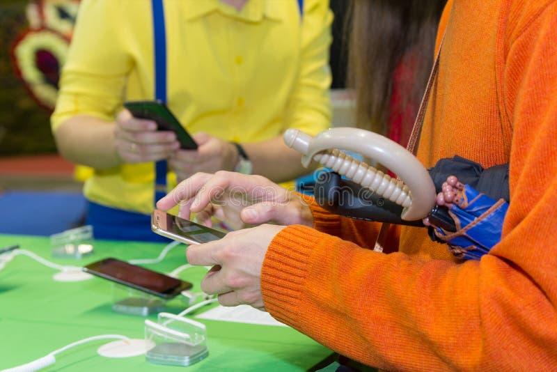 Hände des Käufers, der den Smartphone im Shop wählt lizenzfreie stockfotos