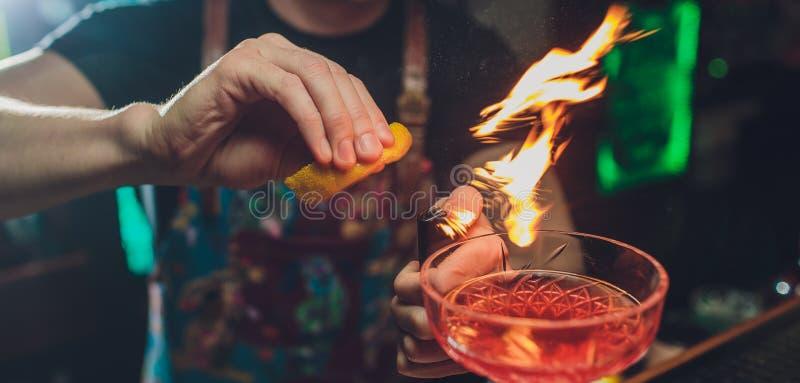 Hände des Kellners s, die ein frisches alkoholisches Cocktail mit einer rauchigen Anmerkung auf dem dunklen Barzähler machen stockbilder