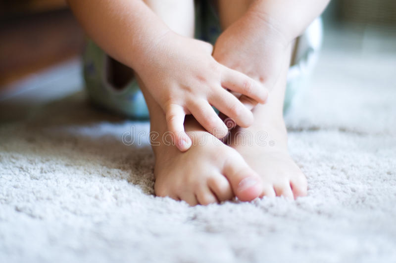 Hände des Kindes, die bloße Füße umfassen lizenzfreies stockfoto