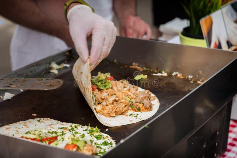 Hände des Kochs Fajitaverpackung mit Rindfleisch- und Gemüsesalat vorbereitend Mexikanische Nahrung Wohlschmeckende Imbisse lizenzfreies stockbild