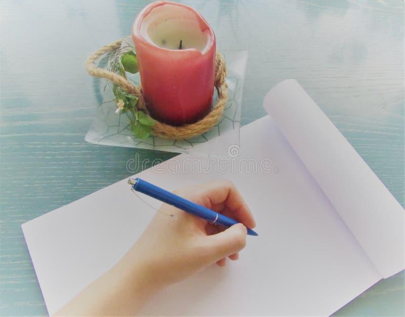 Hände des Mädchenschreibens mit einem blauen Stift im Notizbuch und in der Wüste leuchten Stellung auf hölzernem Hintergrund der  stockfoto