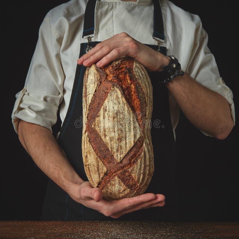Hände des Mannes ovales Brot halten stockfotografie